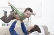 Deutschland, München, Vater spielt mit Jungen auf dem Sofa