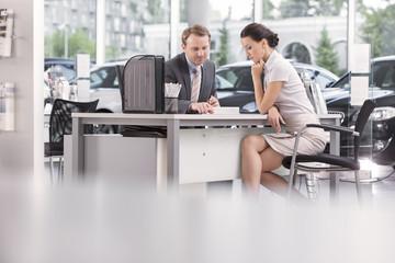 Beim Autohändler, Verkäufer im Gespräch mit Kunden
