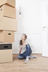 Frau sitzt auf dem Boden neben Stapel Kartons