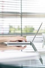 Deutschland, Hannover, Geschäftsfrau mit Laptop auf dem Konferenztisch