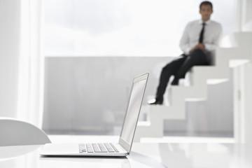 Spanien, Geschäftsmann sitzt auf Treppen, Laptop im Vordergrund