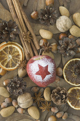 Weihnachtsapfel mit Schnee Sterne, Haselnüsse, Walnüsse, Mandeln, Sternanis, Zimtstangen, getrocknete Orangenscheibe und Tannenzapfen