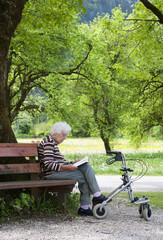 Österreich, Seniorin sitzt auf der Bank und lesen Buch