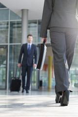Deutschland, Hannover, Geschäftsmann und Geschäftsfrau mit Aktentasche zu Fuß  am Terminal