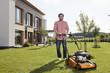 Deutschland, Nürnberg, Senior mit Rasenmäher im Garten