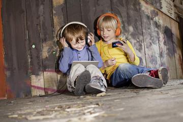 Deutschland, Köln, Jungen hören Musik im Spielplatz