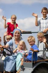 Deutschland, Bayern, Frau mit einer Gruppe von Kindern sitzt auf alten Traktor