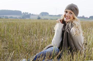 Lächelnde Frau mit Bettdecke und Wollmütze sitzt in einem Stoppelfeld