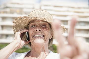 Spanien, Seniorin im Gespräch über Handy