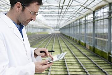 Deutschland, München, Wissenschaftler im Gewächshaus mit Tablet PC Prüfung Beet mit Setzlingen