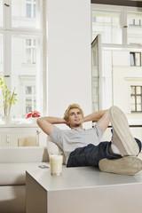Deutschland, Berlin, Junger Mann sitzt im Wohnzimmer