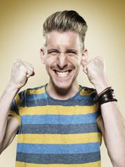 Portrait eines glücklichen jungen Mann ballte die Fäuste