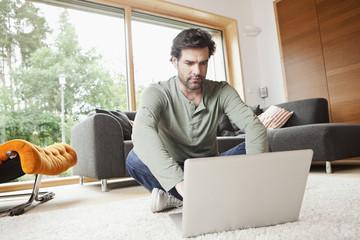 Deutschland, Nürnberg, Senior mit Laptop im Wohnzimmer