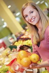 Deutschland, Köln, Junge Frau mit Smartphone und Orangen im Supermarkt