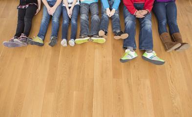 Österreich, Kinder und Teenager sitzen auf einem Holzboden