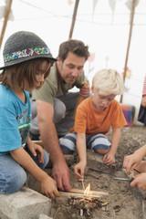 Deutschland, München, Vater mit Kindern bereitet Lagerfeuer im Zelt