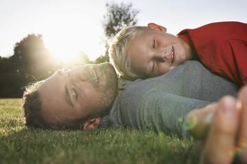 Deutschland, Köln, Vater und Sohn schlafend in der Wiese