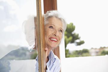 Spanien, Seniorin, die durch Fenster schaut