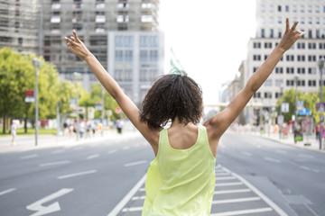 Deutschland, Berlin, Junge Frauen in der Stadt, Victory-Zeichen, Rückansicht