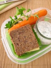 Brotbox mit Vollkornbrot und Möhren mit Kräuter-Joghurt