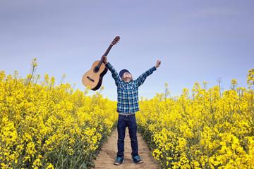 Deutschland, Hamburg, Junge steht Feld mit Akustik-Gitarre