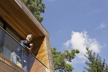 Deutschland, Berlin, Mann stehen auf dem Balkon und entspannend