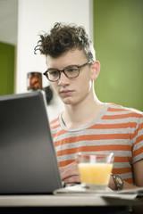 Deutschland, München, Junger Mann mit Laptop im Café