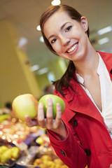 Deutschland, Köln, junge Frau vergleichen Äpfel im Supermarkt