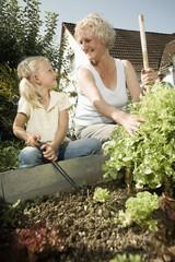 Deutschland, Bayern, Großmutter mit Kindern arbeiten im Gemüsegarten