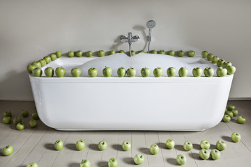 Badewanne mit grünen Äpfeln in Bad gefüllt