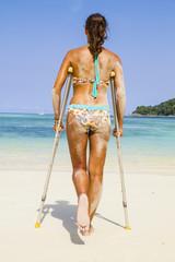 Thailand, Koh Surin Insel, Frau mit Krücken stehen am weißen Sandstrand