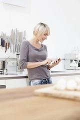 Deutschland, München, Frau mit Handy in der Küche