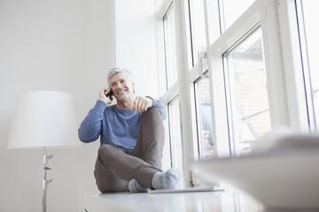 Deutschland, München, Ältere sitzen am Fenster und sprechen über Handy