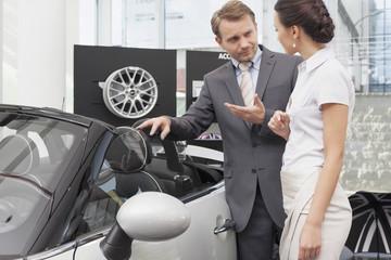 Beim Autohändler, Verkäufer im Gespräch mit Kunden bei Cabrio