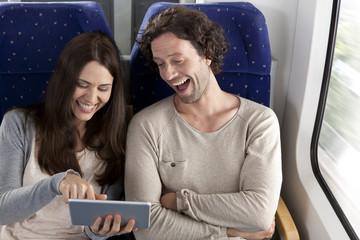 Paar mit Tablet PC in einem Zug