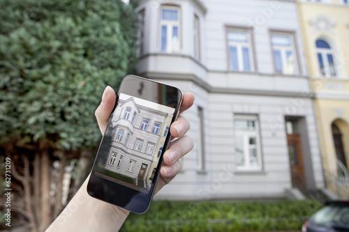 Deutschland, Bonn, Hand mit Smartphone vor dem Haus