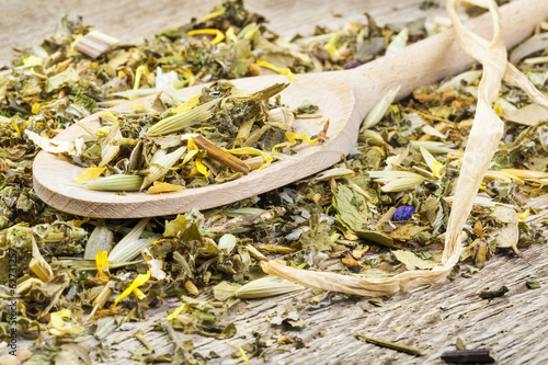 Curative natural herbal tea on wooden spoon on old table