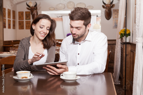 Young woman and man using tablet in coffee shop