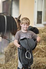 Deutschland, Korchenbroich, Junge hält Sattel