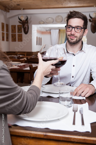 Smiling young man clinking glasses with his girlfriend