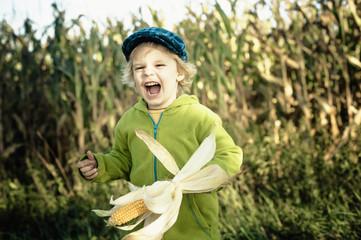 Deutschland, Sachsen, Junge hält Maiskolben und lachen
