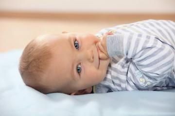Deutschland, Bayern, Baby auf Handtuch liegend lächelnd