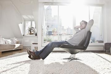 Deutschland, München, Mann sitzt auf Sessel