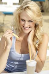 Deutschland, NRW, Haltern, junge Frau mit einem Latte Macchiato
