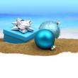 Gift box and Christmas balls on the sand
