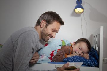 Deutschland, Berlin, Vater, Sohn lesen Buch beim Schlafen