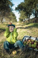 Deutschland, Sachsen, Junge sitzt mit einem Korb voller Äpfel