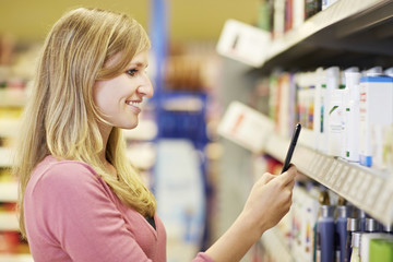 Deutschland, Köln, Junge Frau mit Handy im Supermarkt
