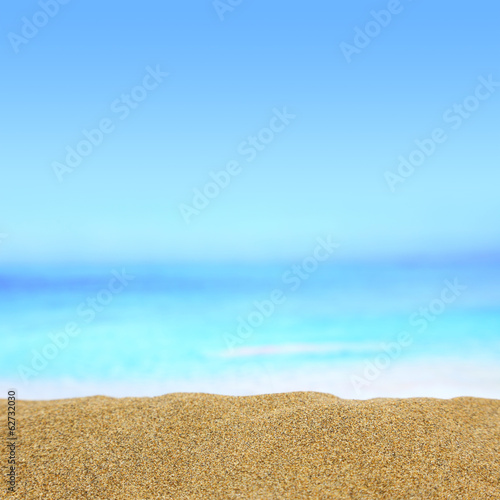 Close up of golden sand with sea on the background