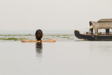 Indien, Kerala, Junge Frau im Schwimmbad Blick auf Hausboot